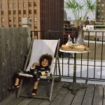Young boy laughing with toy at family reunion on New York City rooftop.